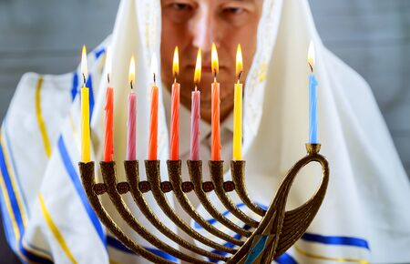 jewish home: Hanukkah, a Jewish celebration. Candles burning in the menorah, the man in the background.