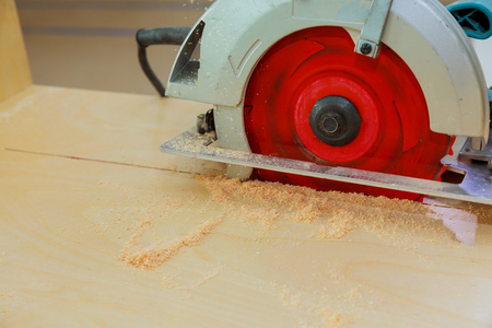 Carpenter using circular saw cutting wooden board in wood workshop. Circular saw cutting wooden Stock Photo