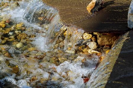 ソースの滝。夏の領土の上の公園で小さなモダンな噴水。小さな人工湖の真ん中に小さい噴水