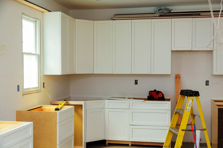 Custom kitchen cabinets in various stages of installation base for island in center Installation of kitchen cabinets