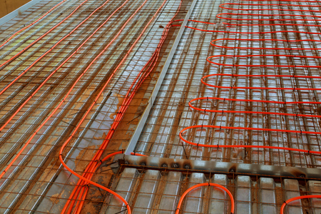 New floor heating system Pipes and heating system at house construction site. floor heating system, the collector and tools Stock Photo