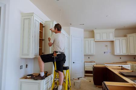 Installatie van de keuken. Werknemer installeert deuren naar keukenkast. Installatie van deuren op keukenkasten