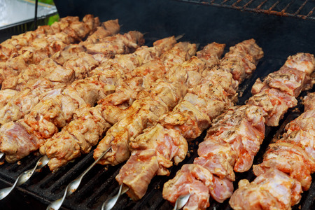 Grilled shish kebab on metal skewer. Chef hands cooking roasted meat barbecue with lots of smoke. BBQ fresh beef chop slices. Traditional eastern dish on charcoal and flame, picnic, street food