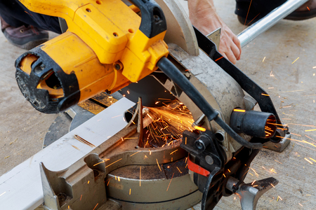 Close-up of worker cutting metal with grinder. Sparks while grinding iron. Low depth of focus Banco de Imagens