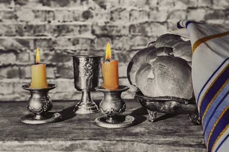 Silver kiddush cup, crystal candlesticks with lit candles, and challah challahs