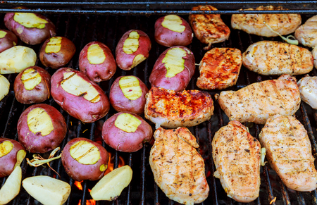 Fried potatoes with bacon on skewers. The concept of eating outdoors in the weekend. Potatoes fry on fire bbq
