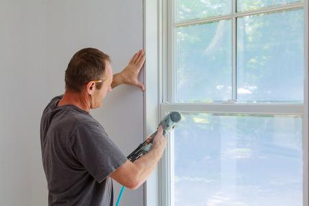 window framing trim wood carpenter using nail gun to moldings on windows framing trim with the warning that using nail gun to moldings on windows framing trim