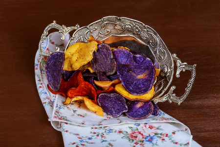 Crunchy appetizer of potato chips made from Crimson red, Purple Majesty and Chipeta, Atlantic potatoes. Potato chips in red, white and blue in a glass bowl on a table.