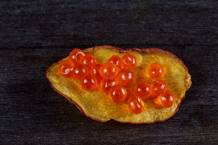 Salmon caviar with potato chips on a black wood Red caviar on potato chips,