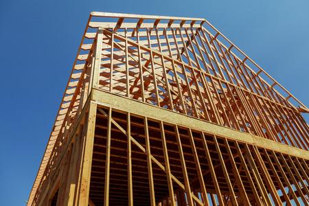 Une maison unifamiliale en construction. La maison a été encadrée et recouverte de contreplaqué. Des piles de planches de bois à l'avant et une pile de 2x4 planches sur le dessus. Banque d'images