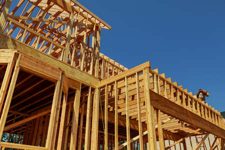 New residential construction home framing against a blue sky and sun New Home Under Construction