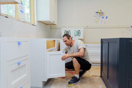 worker installing kitchen cupboard Installation of kitchen. Worker installs kitchen cabinet.