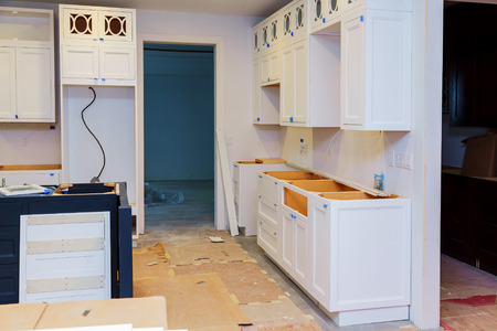 Installation of kitchen. Custom kitchen cabinets in various stages of installation base for island in center Imagens