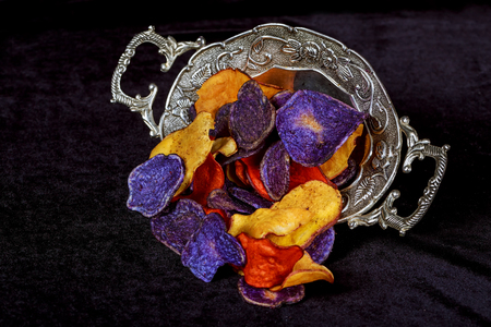 Crunchy appetizer of Potato chips in red, white and blue in a glass bowl on a table. Stock Photo