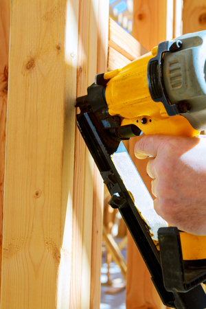 Building contractor worker putting in a interior wall partition nailer wall for the first floor on a new home construction project
