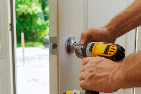 Installation of a lock on the entrance door Hand 's man with screwdriver Installs door knob. 版權商用圖片