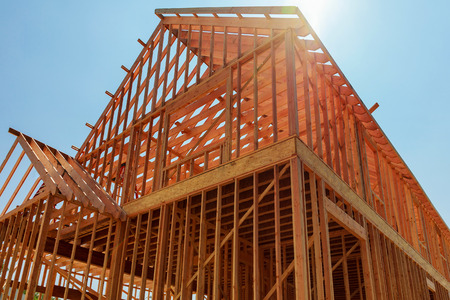 A single family home under construction. The house has been framed and covered in plywood. Stacks of board timber in front and stack of 2x4 boards on the top. Stock Photo