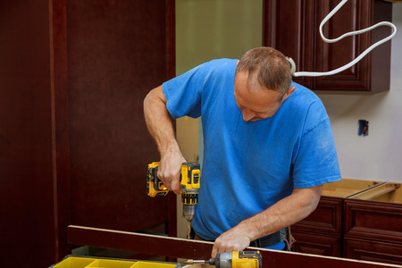 kitchen cabinets: technician man installing kitchen cabinets Installation of kitchen cabinet.