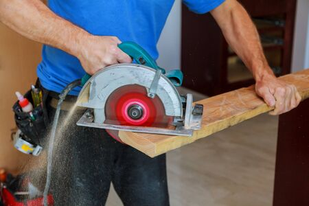 Man using circular saw Close up electric saw to sawing wood board, solf focus.
