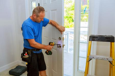 Installatie van een slot op de toegangsdeur Hand man met schroevendraaier Installeert deurknop. Stockfoto