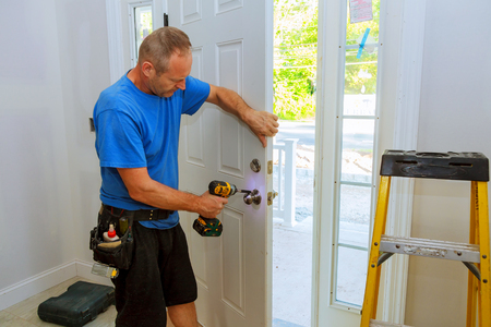 Installation of a lock on the entrance door Hand 's man with screwdriver Installs door knob. Standard-Bild