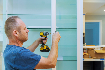 Construction worker sets a new handle a screwdriver installing kitchen cabinets