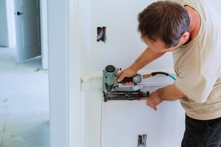 Carpenter using a brad nail gun to complete framing trim Air gun for nailing using nail gun