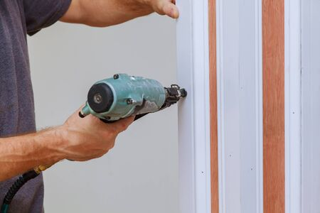 Carpenter using a brad nail gun to complete framing trim Air gun for nailing using nail gun