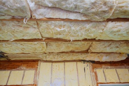 Fibreglass insulation installed in the sloping ceiling of a new frame house. insulation for the home