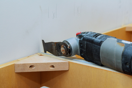 oscillating multi-function power tool on kitchen cabinets framing background Stock Photo