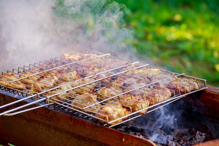 Grilled chicken thigh on the flaming grill chicken meat is baked on fire and smoke