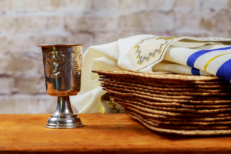 Red kosher wine with a white plate of matzah or matza and a Passover Haggadah on a vintage wood background presented as a Passover seder meal with copy space. Perfect for your Passover design mock up Stock Photo