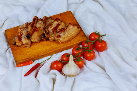 Fresh cooked fried bacon cutting Board tomato hot pepper aged wooden background. copy space.