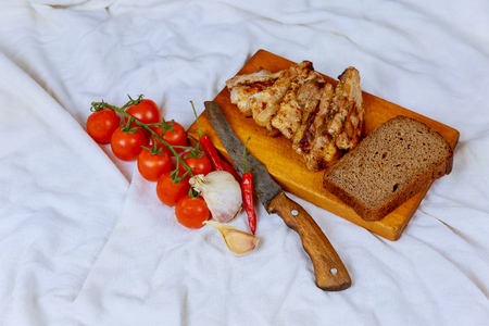 fried bacon on a wooden board with tomatoes and pepper Fried bacon, tomato and garlic on the wooden board.
