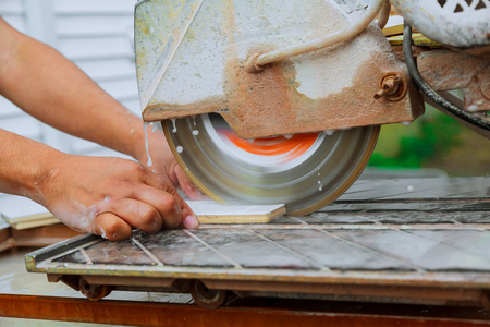 Contractor working on a tile saw The master cuts the tile on the saw Stock Photo