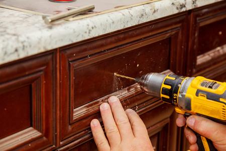 master drills the door in the cabinet door