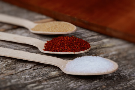 ground spices for meat garlic salt pepper Three spoons with spices are lying on a dark background Foto de archivo