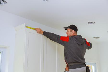 Carpenter Crown Moulding on kitchen cabinets framing trim, with the warning label that all power tools have on them shown illustrating safety concept