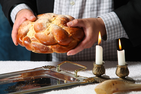Heap of sweet round sabbath challah bread black sesame seeds in vintage metal bowl and on small cutting board over white table