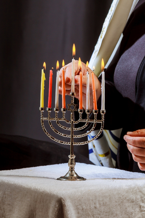man hand lighting candles in menorah on table served for hanukka man lights candles