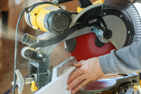 Repair building construction work saw circular saw boards 90059408 handsome young man carpenter using a circular saw while installing wood in new house construction keyboard keysfo Images