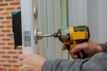 Bringen Sie den Türgriff mit einem Schloss an. Carpenter zieht die Schraube mit einem elektrischen Bohrschraubendreher fest (Nahaufnahme).