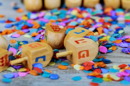jewish holiday Hanukkah with wooden dreidel spinning top on the glitter background Stock Photo