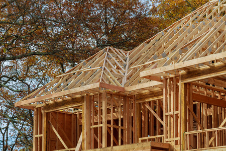 New residential construction home framing against a The house is new in wood roofing