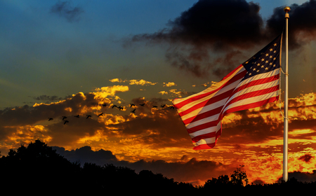 American flag on flagpole waving in the wind against clouds, American flag in front of bright sky