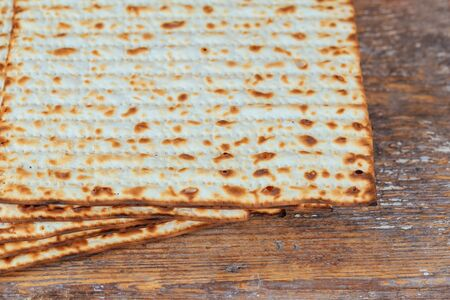 Jewish kosher matzah closeup on paper on a wooden table. horizontal view from above