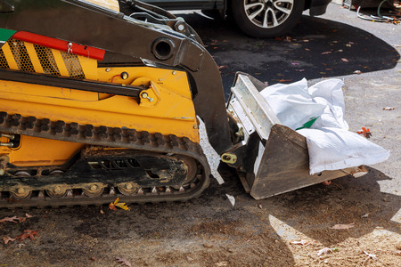 Small excavator removes broken asphalt and gravel on construction site.