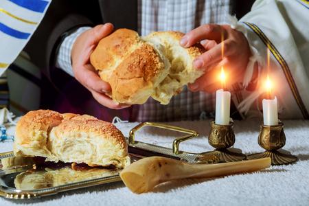 Heap of sweet round sabbath challah bread black sesame seeds in vintage metal bowl A man breaks Saturday's festive bread