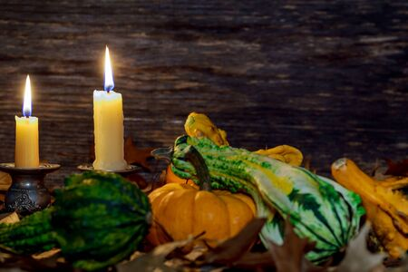 Autumn thanksgiving decor setting with candles and pumpkin