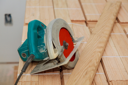Electric saw on wood floor in progress cut old parquet floor with electric saw Stockfoto